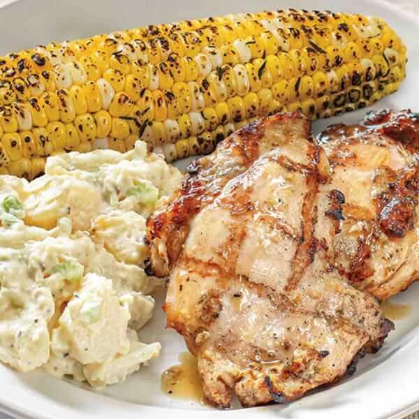 Lemon Garlic Chicken meal with corn on the cobb and potato salad